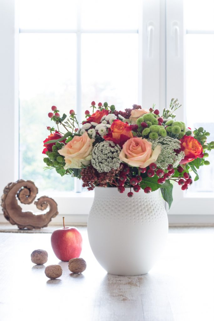 Blumendeko im Herbst mit Rosen und Beeren