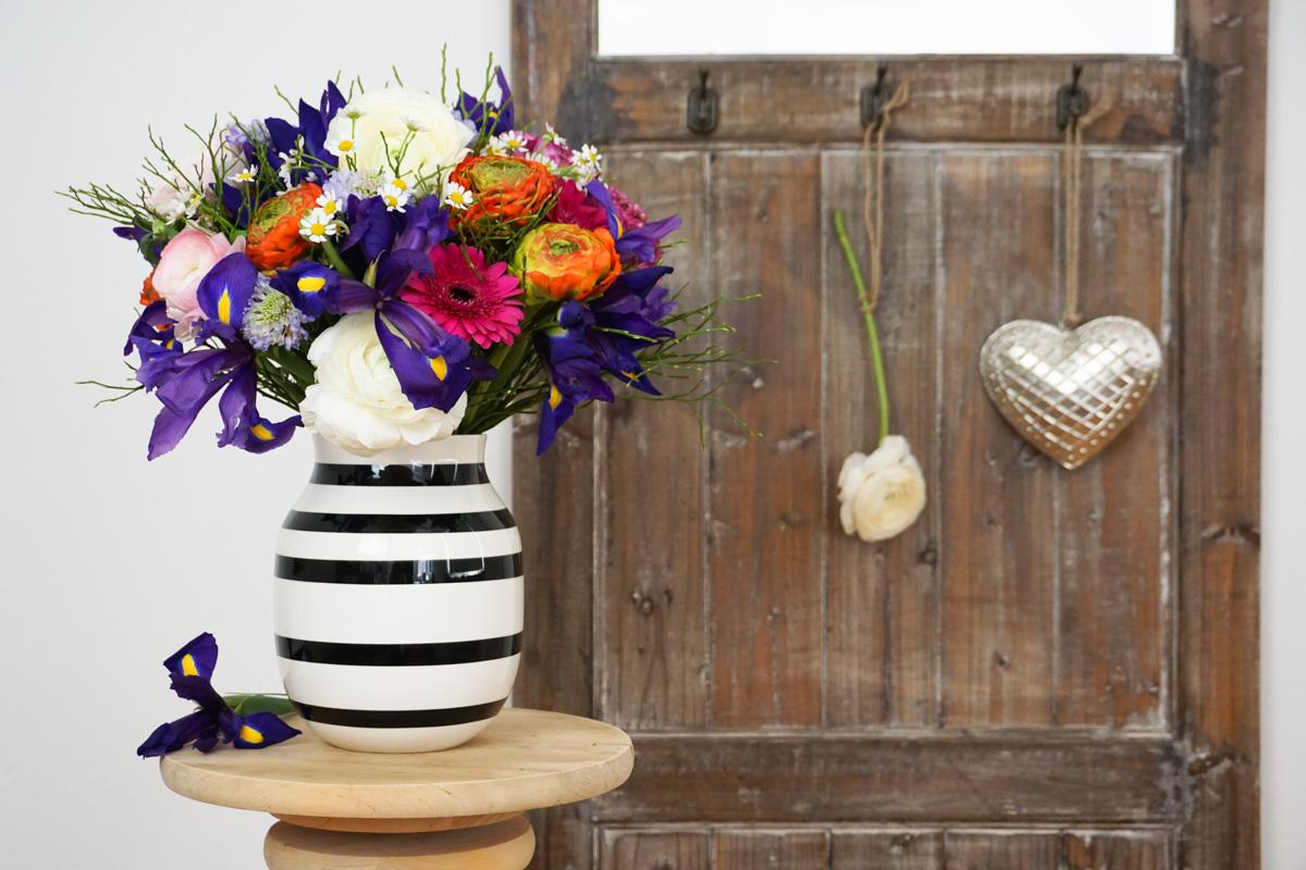 Bunte Farben für den Frühling: lilafarbene Iris, weiße & orangerote Ranunkeln, pinkfarbene Gerbera und wilde Kamille.